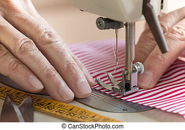 Hands at sewing machine holding some fabric