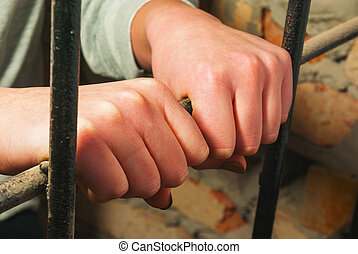 Hands behind the bars