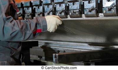 Hands bend sheet metal worker in the factory - hands that...