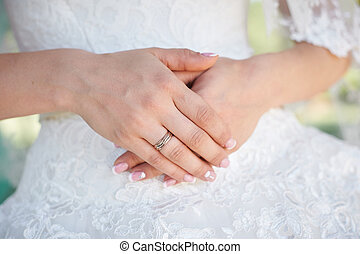 hands bride with gold ring on background of white dresses