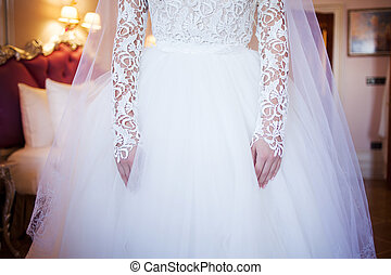 Hands bride with manicure. Wrist on the background of white lace dress covered with a veil
