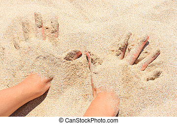 Hands buried in sand