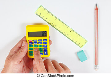 Hands calculate using a pocket digital calculator over workplace of the engineer