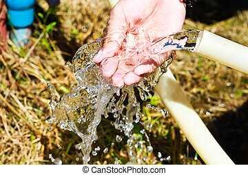 hands catching the hose of water