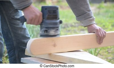 Hands changing sand paper on random orbital sander and...