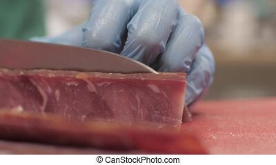 Hands chef cook using knife for cutting meat while cooking in kitchen close up