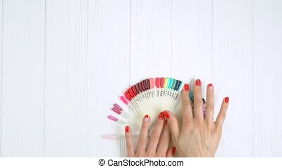 Hands choose blue nail color sample. Young woman hands with...
