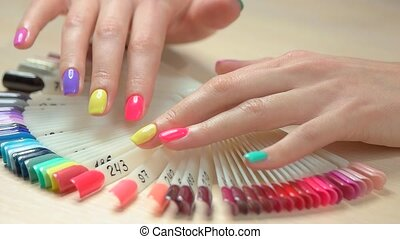 Hands choosing nail color, slow motion. Beautiful female...