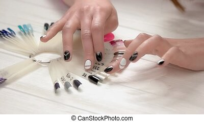 Hands choosing nail color, slow motion. Young woman hands...