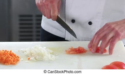 Hands chopping tomato. Man cutting vegetable close up.