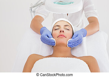 Hands cleaning woman's face with cotton swabs at spa center