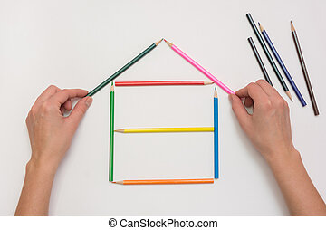 Hands close-up build a house on a piece of paper from the crayons