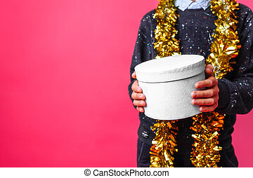 Hands close-up, holding gift box on red background . The concept of Christmas to give gifts