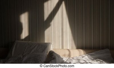 Hands closing window curtain from warm morning light in a bedroom. Blackout curtain. Self isolation. Quarantine.