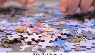 Assembling jigsaw puzzle. Looking for right piece of puzzle. Leisure activity. Achieving the goal step by step Love concept. Engaging in successful work finding business solution, corporate unity
