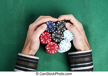Hands collecting a big pile of poker chips