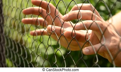 Hands compressed metal fence. Help the person. Break loose