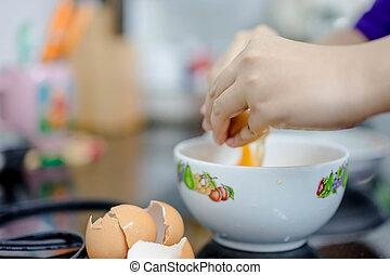 cracking an egg  - hands cracking an egg into a glass bowl