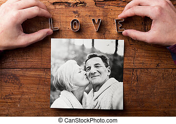 Hands creating Love sign. Picture of senior couple. Studio shot,