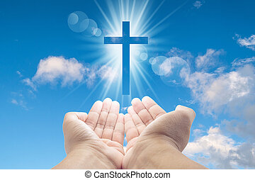hands cupped with a shining white cross hovering above on a sunny blue daytime sky