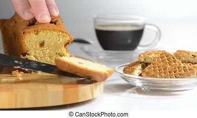 Hands cut cake with raisin on a chopping board a sharp knife...