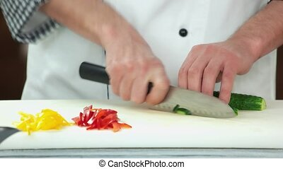 Hands cutting cucumber.