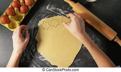 hands cutting dough with star shaped cutter - cooking food, ...