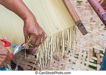 Hands cutting mat weaving.