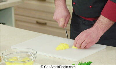 Hands cutting potato with a knife