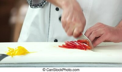 Hands cutting red paprika.
