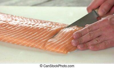 Hands cutting salmon. Raw fish close up.