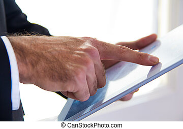 Hand's detail of Businessman using a digital tablet