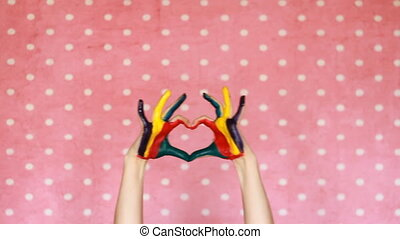Hands dirty painted colorful show heart. The concept of...