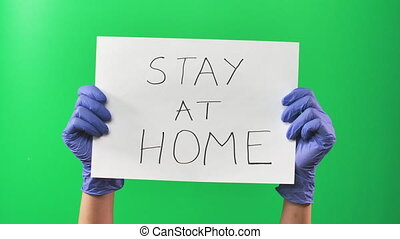 Hands doctor woman in blue gloves holding a sign with an appeal to stay at home. Green screen. Close up