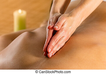 Hands doing Ayurvedic massage on female spine.