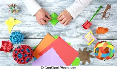 Hands doing origami from green paper. Set of origami...