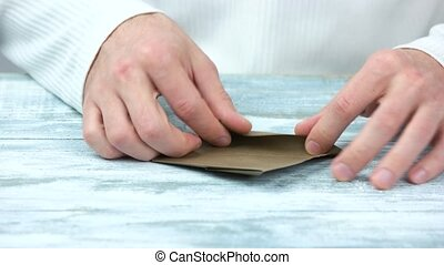 Hands doing origami toy from brown paper. Traditional...