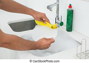 Hands doing the dishes at kitchen sink