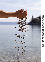 Hands dropping small stones - Symbolic concept of peace, ...