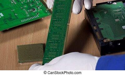 hands examining computer RAM memory module. Computer...