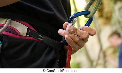 Hands fasten carabiner in climber harness.
