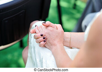 hands folded in her lap with a manicure Women