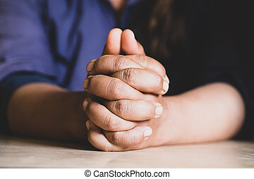 Hands folded in prayer on a Holy Bible in church concept for...