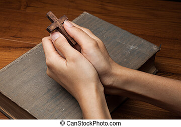 Hands folded in prayer over Holy Bible