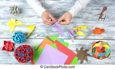 Hands folding origami cranes, fast motion. Male hands making...