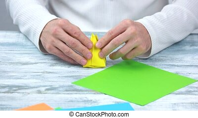 Hands folding origami tulip bulb. Art of paper folding...