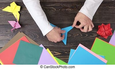 Hands forming blue origami crane. Man doing origami from...