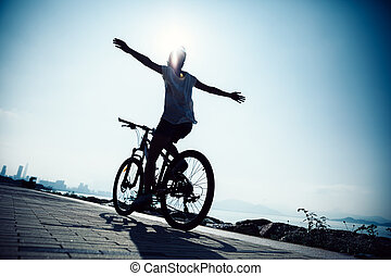 Hands free cycling woman riding Mountain Bike on sunrise seaside
