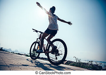 Hands free cycling woman riding mountain mike on sunrise seaside