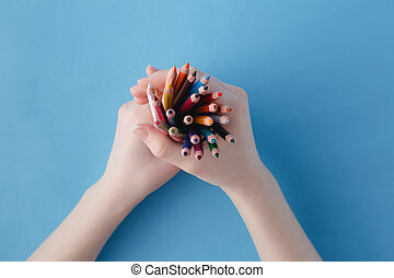 Hands full of bunch colored pencils